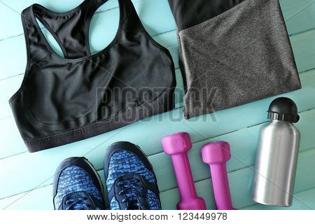 Athlete's set with female clothing, dumbbells and bottle of water on blue wooden background