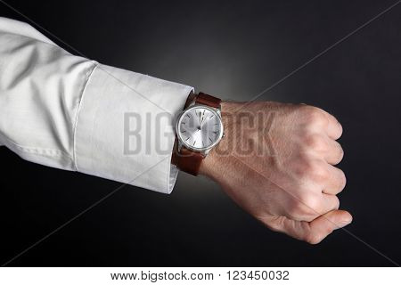 Modern watch on a businessman's wrist over black background