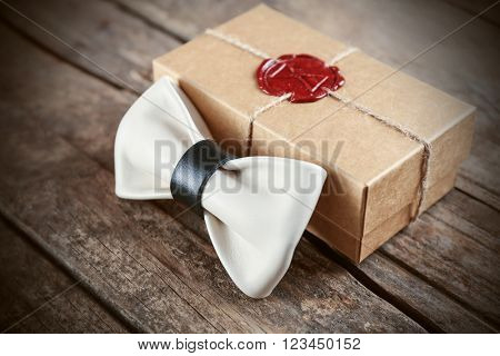White and black leather bow tie and cardboard gift box with red seal on wooden table, close up