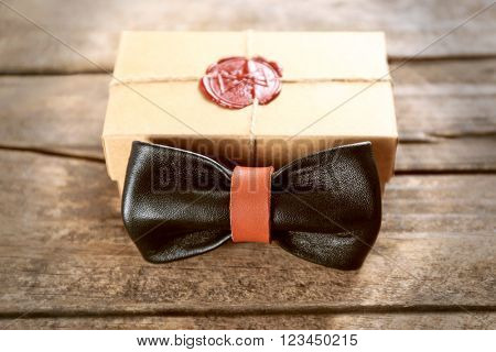 Black and brown leather bow tie and cardboard gift box with red seal on wooden table, close up