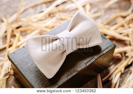 White leather bow tie with special packaging on a thatch, close up