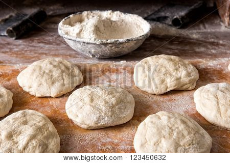Raw Bread Rising On Table With Bowl Of Flour