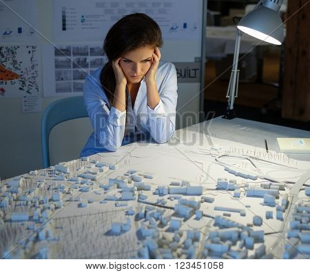 Tired young architect having a problem with her technical layouts and blueprints in a architect studio.