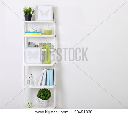 White bookcase with books and accessories in the room