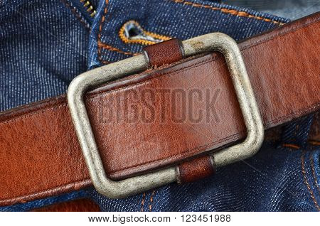 Blue jeans with natural leather belt close up