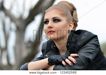 Closeup portrait of fashionable, glamour, beautiful, attractive, pretty, nice, lovely, good, adorable adult professional biker girl with smokey eyes, red lips, creative hairstyle, interesting look looks forward.
