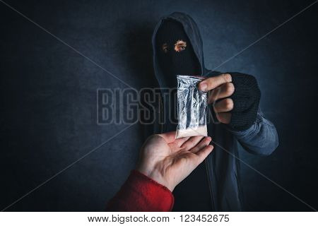 Drug dealer offering narcotic substance to addict on the street unrecognizable hooded criminal selling drugs in dark alley.