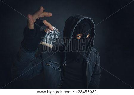 Drug dealer offering narcotic substance to addict on the street unrecognizable hooded criminal selling drugs in dark alley addicted person point of view image