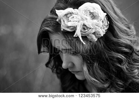 The portrait of sad, upset, unhappy beautiful, attractive, cute, pretty, nice girl with wreath, flowers. Black and white photo. Beautiful girl think about problems, worry about her boyfriend, broken heart, lovely