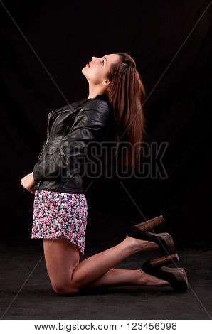 Confident Young Woman With Leather Jacket Lets Her Head Back And Posing On Her Knees