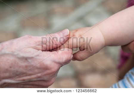 hands of baby grandson and old grandmother concept of family relationship and passage of time