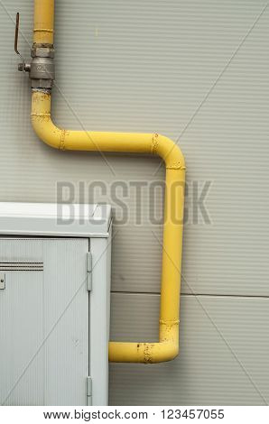 Yelow Pipes And Gas Meter On Gray Wall