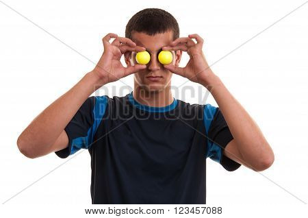 Young smiling male golf player covering his eyes with two yellow golf balls on white background