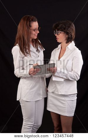 Two Smiling Female Medical Doctor Discussing Together On Medical Exam Over Black Background
