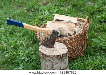 An axe stuck in a log in front of basket with logs fire ** Note: Shallow depth of field