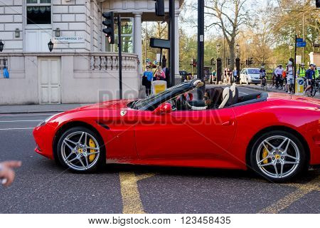 LONDON UK - April 14 2015: View of red Ferrari in the street. Woman drives a Ferrari