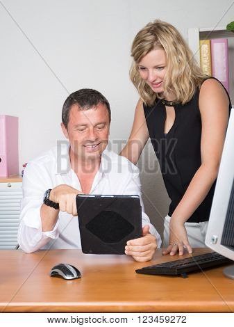 Top view of male and female business partners analysing statistical annual report represented in graphs on digital tablet.
