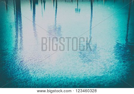 blue summer  tiled pool with  reflections of palm trees , retro toned