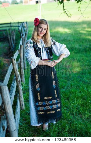 Full Length Of Young Beautiful Woman With Red Flower In Her Hair Posing In Romanian Traditional Cost