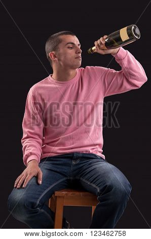 Young man drinking alcohol on black background