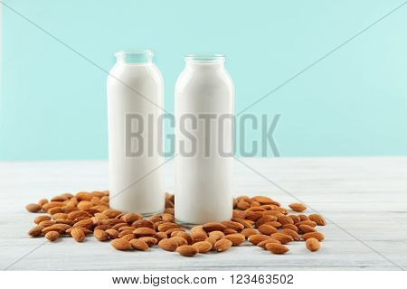 Bottles with milk and almond nuts on blue napkin