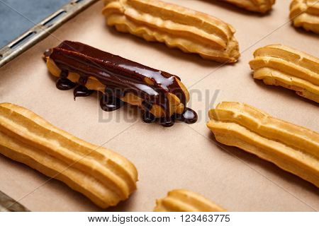 Eclairs with chocolate and whipped cream preparing on baking sheet background. Traditional homemade French cuisine dessert.