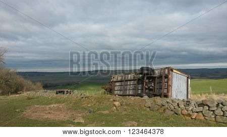 Farm tractor trailor lying on its side in Wooler