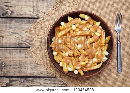 Poutine traditional Canadian meal with fries, curd cheese and sauce on vintage wooden table background. Rustic style.