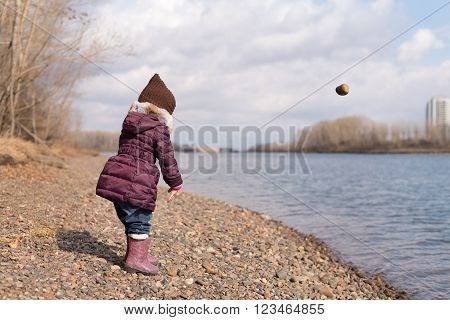 Little girl throwing a stone into river on a sunny day