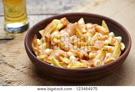 Poutine Canadian traditional fast food with fries, curd cheese, gravy and beer on vintage wooden table background. Rustic style