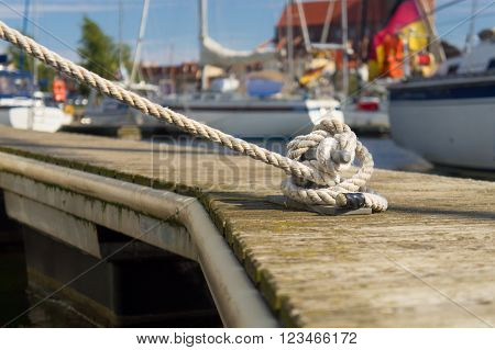Mooring rope wrapped around the cleat on pier