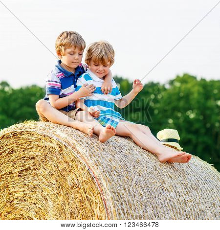 Two little children and friends sitting on hay stack or bale and speaking on yellow wheat field in summer. Active outdoors leisure with children on warm summer day.