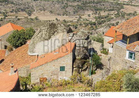 background landscape view of an amazing house with a boulder in the roof in the Portuguese village of Monsanto
