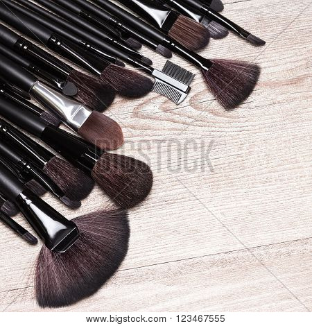 Set of various makeup brushes: for applying foundation, powder, blush, eyeshadow, eyebrow brushes, fan brush and others. Professional tools of make-up artist on shabby wooden surface. Copy space