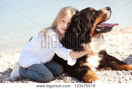 Little kid girl holding bernese mountain dog at beach