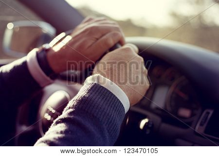Senior hands holding steering wheel while drives a car.