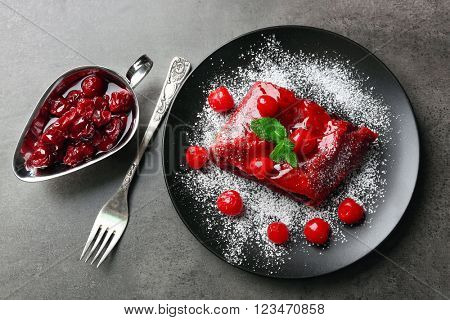 Delicious powdered cherry strudel with mint on plate