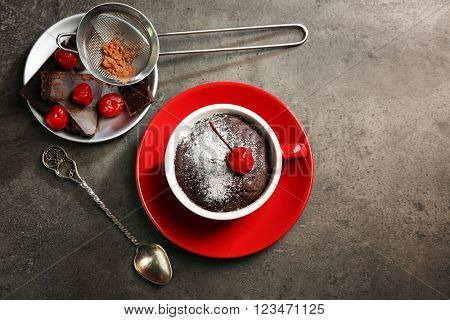 Chocolate cake in a red mug  with a cherry on top, top view