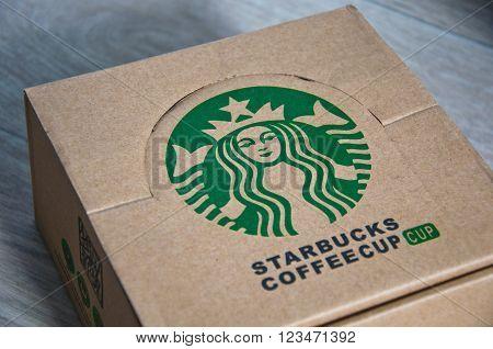 Kiev Ukraine - February 16 2016: Square paper company box with stylish round green logo of Starbucks coffeehouse corporation