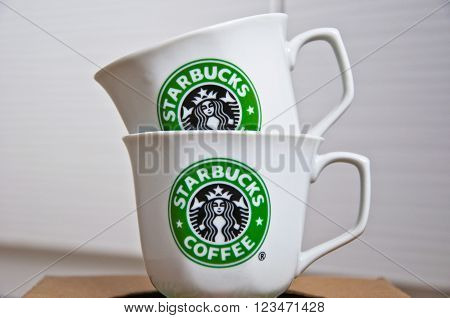 Kiev Ukraine - February 16 2016: Two ceramic shiny company white cups with stylish round green logo of Starbucks coffeehouse corporation on paper box ** Note: Visible grain at 100%, best at smaller sizes