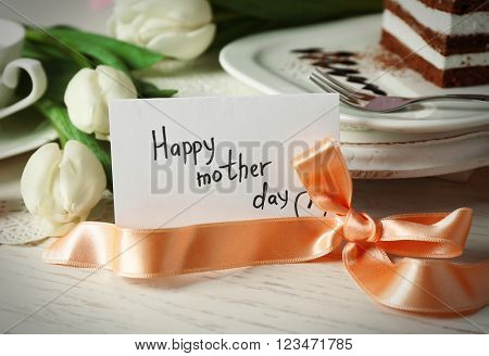 Happy mother day greeting with tulips, cup of tea and delicious cake on wooden table closeup