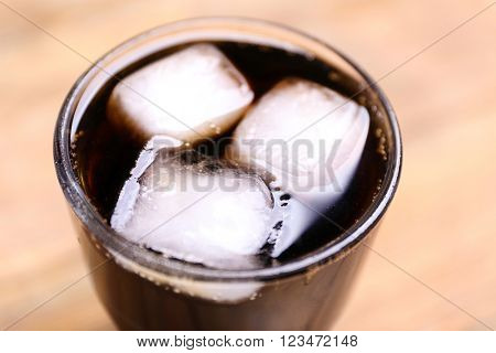 Glass of water with ice blocks  on wooden background, close up