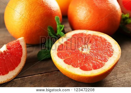 Sliced grapefruits with mint on wooden background, close up