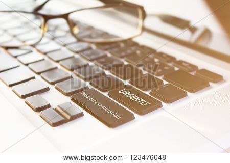 Text physical examination and urgently on notebook keyboard with blurred eyeglasses and copy space, health concept or working too hard ** Note: Shallow depth of field