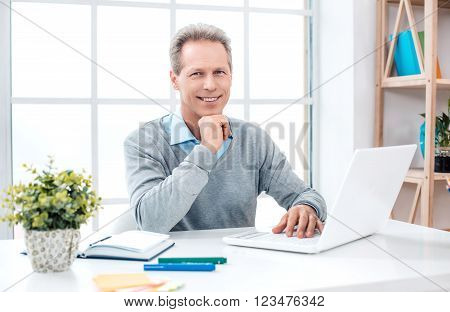 Stylish adult businessman while working day in office. Businessman with laptop, looking at camera and smiling. Office interior with bookcase and big window