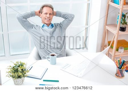 Stylish adult businessman while working day in office. Businessman with laptop, relaxing, looking at camera and smiling. Office interior with bookcase and big window