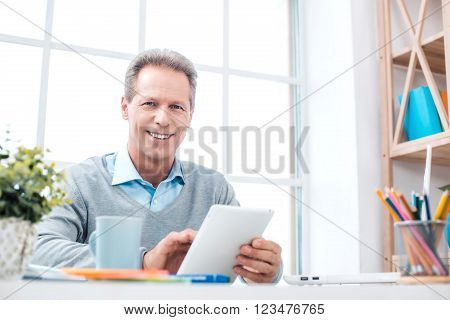 Stylish adult businessman while working day in office. Businessman with tablet computer, looking at camera and smiling. Office interior with bookcase and big window