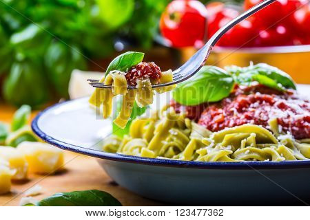 Pasta. Italian and Mediterranean cuisine. Pasta Fettuccine with tomato sauce basil leaves garlic and parmesan cheese. An old home kitchen with old kitchen utensils.