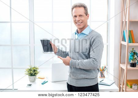 Stylish adult businessman while working day in office. Businessman with laptop using tablet computer, looking at camera and smiling. Office interior with big window and bookcase