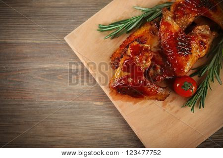 Grilled chicken wings with garden-stuff on cutting board